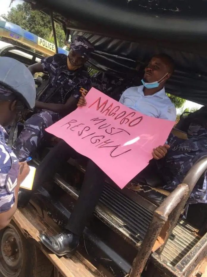 Mike Mutyaba on a police Vehicle with the Placard.