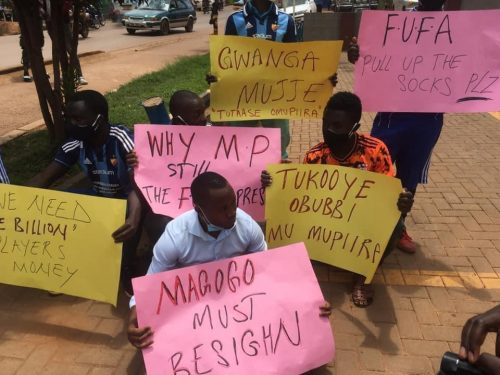 Mike Mutyaba in a Sky Blue Shirt and the group demonstrating at FUFA House.